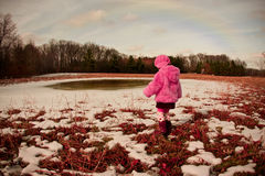 Pretty in pink. Picture of a child walking in dried grass field in winter Royalty Free Stock Photos