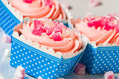 Pretty pink cupcakes. Delicious pink cupcakes in blue and white boxes, decorated with turkish delight Royalty Free Stock Image