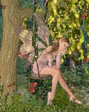 Pretty Pink Fairy Daydreaming on a Woodland Swing. Pretty blonde fairy with pink dress and wings sitting day-dreaming on a swing in a sunny woodland surrounded Stock Image