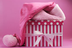 Pretty pink feminine santa hat and polka dot and stripe gift box Stock Photos