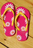 Pretty Pink Flip Flops. Colorful pink and daisy flip flops on patio deck Royalty Free Stock Photo