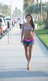 Pretty in pink and heels on the beach side walk. Royalty Free Stock Photo