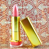 Pretty pink lipstick still life. A pink nude lipstick in a gold coloured container with a damask background Royalty Free Stock Images