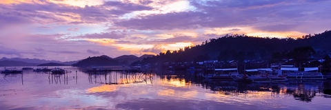 Pretty Pink orange Sky cloudscape over an island. With reflection and wooden traditional filipino boats at Sunset on the Island of Coron, Palawan, Philippines Stock Images