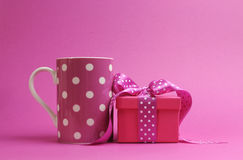 Pretty pink polka dot coffee mug and pink present gift. Stock Photo