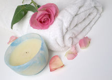 Pretty Pink rose spa. Pink rose and petals with white towel and ceramic candle to show natural beauty and spa treatments Royalty Free Stock Images