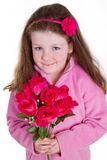 Pretty in pink. Young girl holding a bunch of artifical roses and looking at the camera Stock Photos