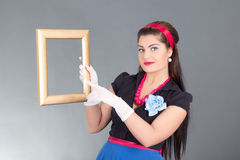 Pretty pinup girl with photo frame Stock Images