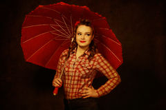 Pretty pinup girl in retro vintage 50`s style with red umbrella Stock Images