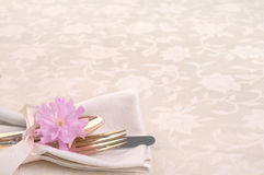 Pretty Place Setting with Fork, Knife, spoon, cherry blossom on Cream Tablecloth. Horizontal with silverware on napkin on bottom left side on off white damask Royalty Free Stock Photo