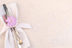 Pretty Place Setting with Fork, Knife, spoon, cherry blossom on Cream Tablecloth. Horizontal with silverware on napkin on left side at an angle on off white Stock Photos