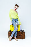 Pretty playful girl in colorful clothes by wooden chests Royalty Free Stock Photo