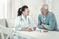 Pretty pleasant nurse giving advices and writing it. New recommendations. Mature pretty pleasant nurse sitting in the room by the table with her patient giving royalty free stock image