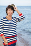 Pretty pleased elderly woman in sea suit on beach Stock Images