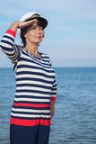 Pretty pleased elderly woman in sea suit on beach Stock Photo