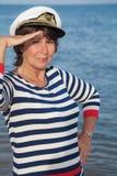 Pretty pleased elderly woman in sea suit on beach Stock Photos