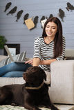 Pretty pleased woman petting her dog Stock Image