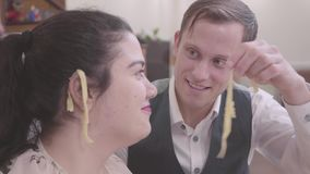 Portrait pretty plump woman with her boyfriend close up at home. Cute slim blond man hanging noodles on the ears of his stock video