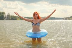 Pretty Plus Size Redheaded Woman Swimming With Blue Life Ring In The Lake Stock Photo
