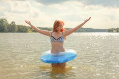 Pretty Plus Size Redheaded Woman Swimming With Blue Life Ring In The Lake Stock Photos