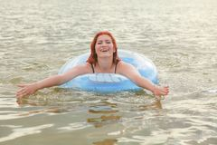 Pretty Plus Size Redheaded Woman Swimming With Blue Life Ring In The Lake Stock Photography