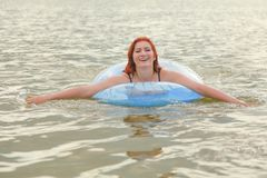 Pretty Plus Size Redheaded Woman Swimming With Blue Life Ring In The Lake Royalty Free Stock Photo