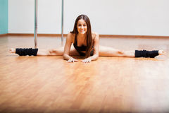 Pretty pole dancer doing a split. Happy young woman stretching and doing a leg split during a pole fitness class Stock Photos