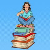 Pretty Pop Art Young Woman Sitting on the Stack of Books and Reading Book with Hand Sign Thumb Up Royalty Free Stock Photos