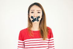 Pretty portrait of asian girl in studio with black tape over her. Mouth over white background Stock Photography