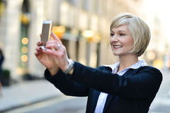 Pretty posing capturing a self shot. Corporate lady clicking her pic, outdoors Stock Images