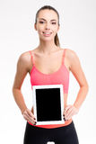 Pretty positive fitness girl holding blank tablet computer screen Royalty Free Stock Photo