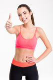 Pretty positive smiling sportswoman in tracksuit showing thumbs up Stock Photos
