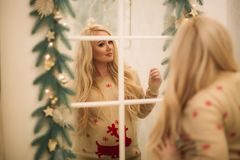 A pretty pregnant blonde in a Christmas sweater stands near the mirror. Winter Royalty Free Stock Image