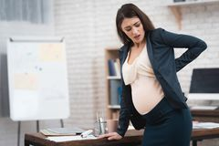 Pretty pregnant girl is experiencing labor in office. Pregnant in office. Pregnant belly. Pregnancy. Pregnant in office Stock Image