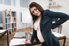 Pretty pregnant girl is experiencing labor in office. Pregnant in office. Pregnant belly. Pregnancy. Pregnant in office Stock Photography