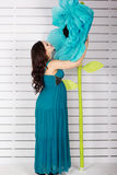Pretty pregnant girl staying near paper blue flowers Stock Photography