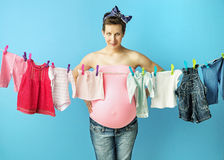 Pretty pregnant mom doing the laundry Stock Images