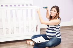 Pretty pregnant woman assembling a crib. Cute young pregnant woman using a screwdriver and assembling a baby crib at home stock photos