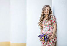 Pretty pregnant woman with a bunch of flowers Stock Image