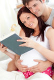 Pretty pregnant woman and of her husband reading Royalty Free Stock Image