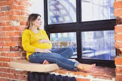 Pretty pregnant woman indoors sitting near window. Portrait of a pretty pregnant woman indoors sitting near window Stock Photo