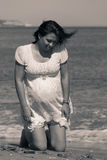 Pretty pregnant woman kneeling down on the beach Stock Photography