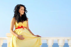 Pretty pregnant woman over sky in yellow dress. Love stock photography