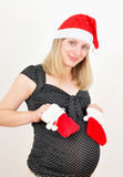 Pretty pregnant woman in santa claus hat royalty free stock image