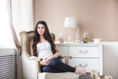 Pretty pregnant woman sitting in armchair Royalty Free Stock Images