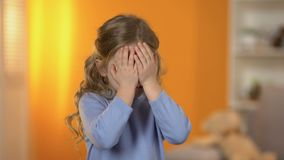 Pretty preschool girl closing eyes with hands, suffering bullying, no friends. Stock footage stock video