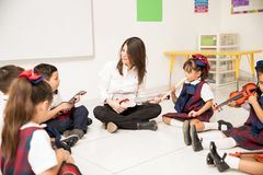 Happy music teacher in preschool. Pretty preschool teacher teaching music to  a group of students sitting on the classroom floor Stock Photos