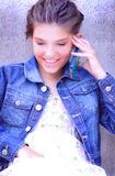 Pretty Preteen Communicating. A closeup of a sweet typical young little brunette preteen girl wearing a denim jean jacket talking on the phone. Shallow depth of Royalty Free Stock Image