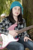 Pretty Preteen Girl. Young preteen girl holding an electric guitar in the forest Royalty Free Stock Photo