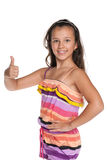 Pretty preteen girl holds her thumb up. A pretty preteen girl holds her thumb up against the white background Royalty Free Stock Photos